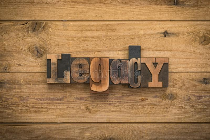 Legacy, word written with vintage letterpress printing blocks on rustic wood background. Legacy, single word written with vintage letterpress printing blocks on royalty free stock photos