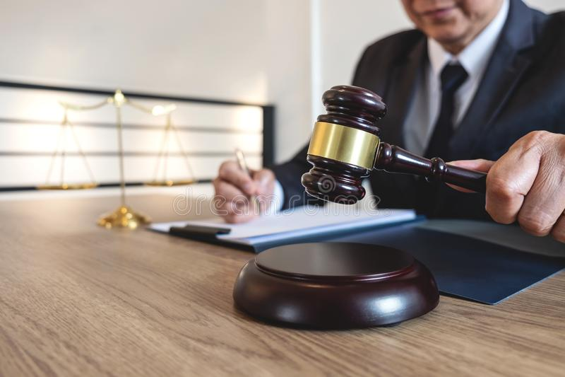Legal law, advice and justice concept, counselor lawyer or notary working on a documents and report of the important case and woo. Den gavel, brass scale on royalty free stock images