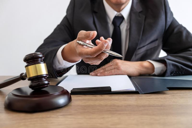 Legal law, advice and justice concept, counselor lawyer or notary working on a documents and report of the important case and. Wooden gavel, brass scale on royalty free stock image