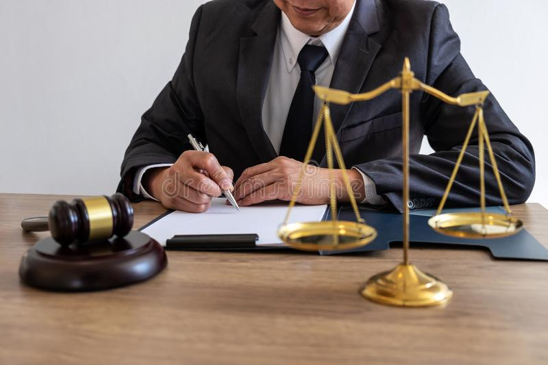 Legal law, advice and justice concept, counselor lawyer or notary working on a documents and report of the important case and. Wooden gavel, brass scale on royalty free stock images
