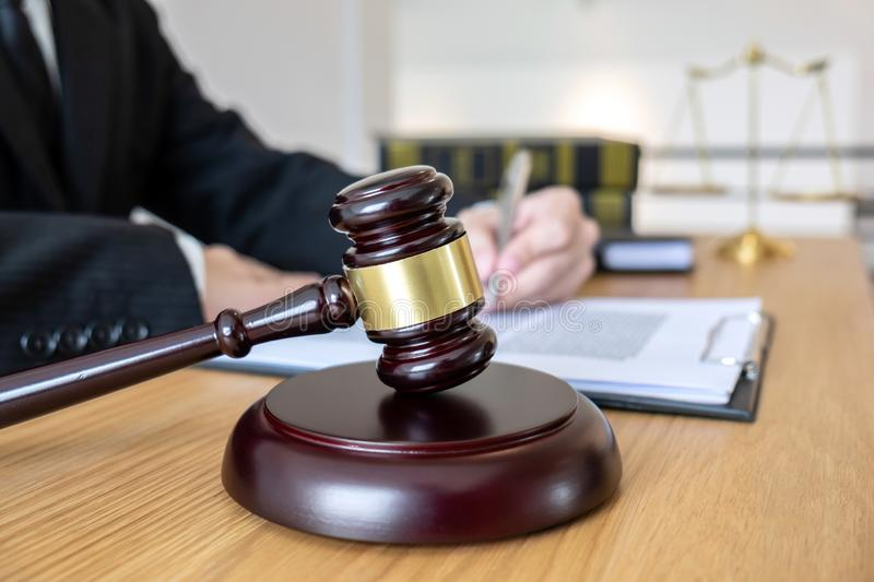 Legal law, advice and justice concept, male lawyer or notary working on a documents and report of the important case and wooden g. Avel, balance on table in stock image