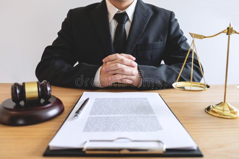 Legal law, advice and justice concept, male lawyer or notary working on a documents and report of the important case and wooden g. Avel, balance on table in stock photo