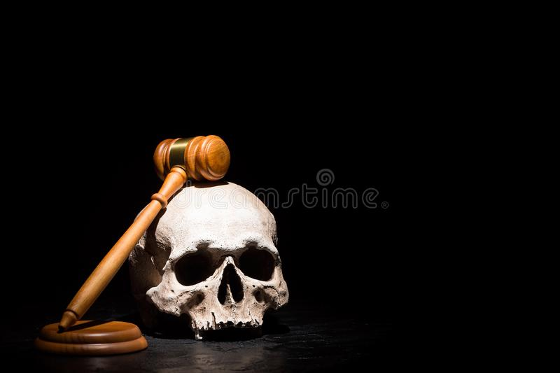 Legal law, justice and murderment concept. Wooden judge gavel hammer on human skull against black background. Free space stock photos
