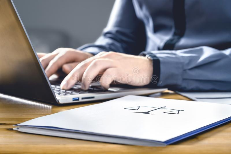 Legal worker in law firm with laptop computer. Attorney, prosecutor or solicitor working on a legislation case. Lawyer or secretary writing paper document stock photography