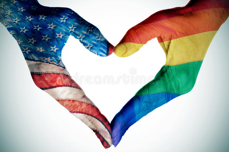 Legalization of the same-sex marriage in the United States. Woman hands forming a heart patterned with the rainbow flag and the flag of the United States royalty free stock photo