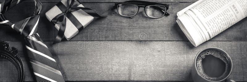 Legame, cinghia e contenitore di regalo con i vetri di lettura, i giornali ed il caff? immagini stock libere da diritti