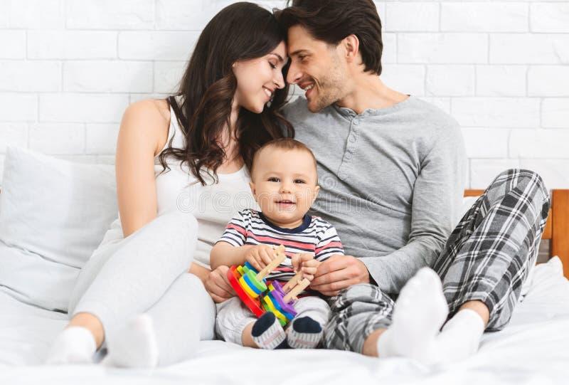 Legame felice dei genitori, bambino adorabile che gioca con il giocattolo fotografia stock libera da diritti