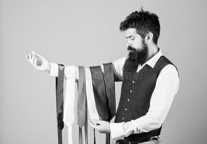 Legame scelto che ha i colori del vostri vestito e camicia come pure almeno altro un colore per fornire un accento Uomo barbuto fotografia stock