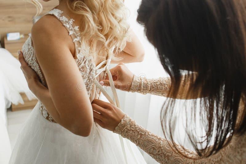 Legami della damigella d'onore un vestito dal pizzo di nozze alla sposa immagini stock