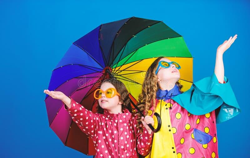 Legami di famiglia Piccole ragazze in impermeabile piccole ragazze felici con l'ombrello variopinto Protezione di pioggia Rainbow fotografia stock libera da diritti