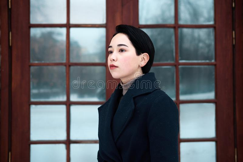 Legant millennial young woman wearing blue coat in cool winter day stock photo