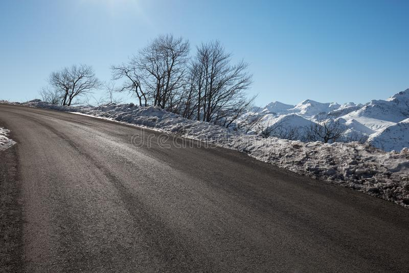 Lege alpiene bergweg in de winter, blauwe hemel stock afbeeldingen