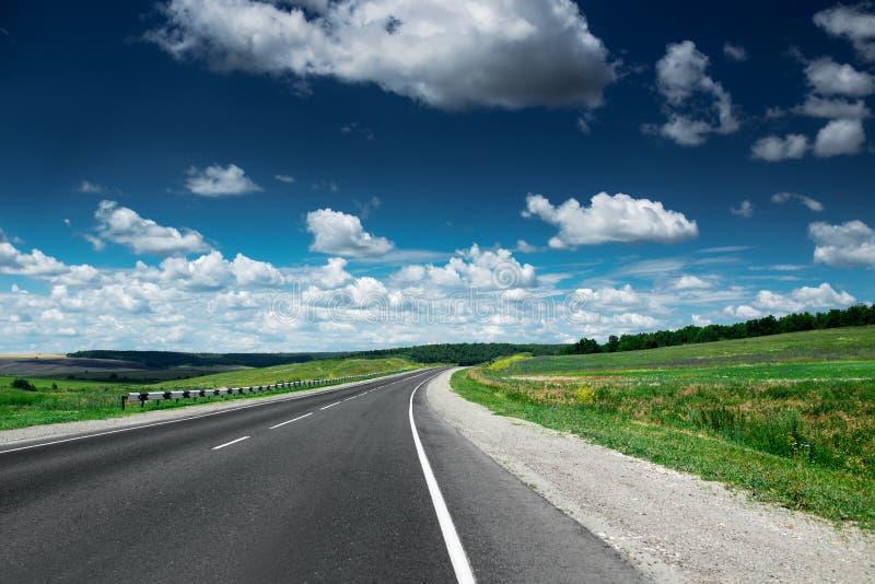 Lege asfaltweg bij dag Mooi aardlandschap stock afbeeldingen
