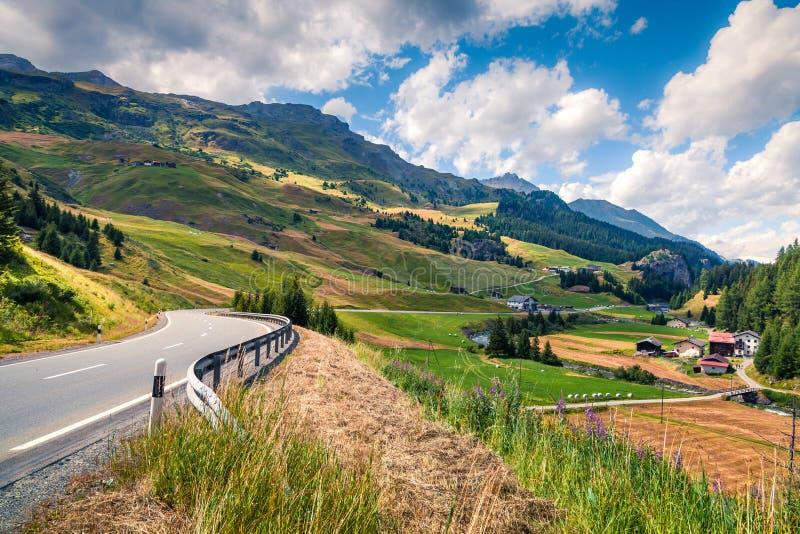Lege asfaltweg met kleurrijke bewolkte hemel in de Zwitserse Alpen stock fotografie