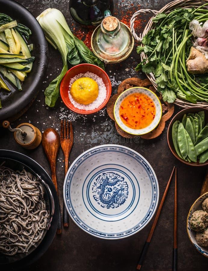 Lege Aziatische kom met eetstokjes en ingrediënten voor noedelsmaaltijd met groene groenten en soba op donkere rustieke achtergro royalty-vrije stock afbeelding