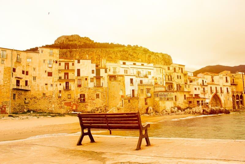Lege bank op pijler in Cefalu, Sicilië, Italië in oranje zonlicht met historische gebouwen op de overzeese kustzonsopgang, zonson stock afbeeldingen