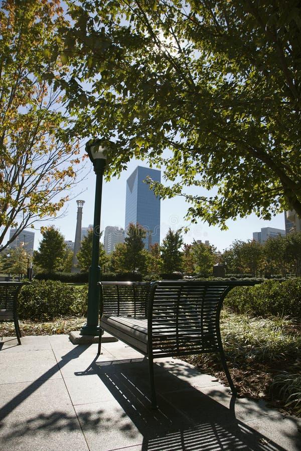 Lege bank in stedelijk park stock afbeeldingen