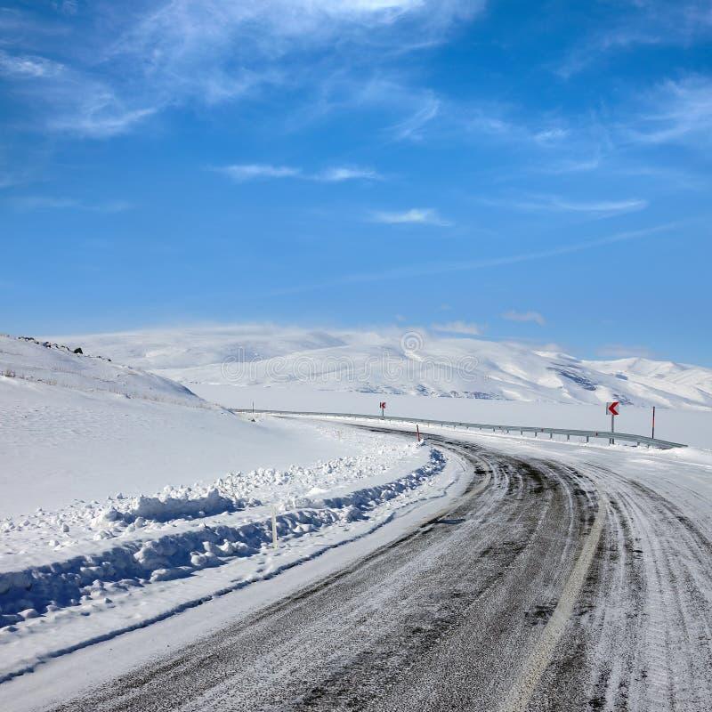Lege bevroren asfaltweg en sneeuw behandeld landschap met mounta stock fotografie