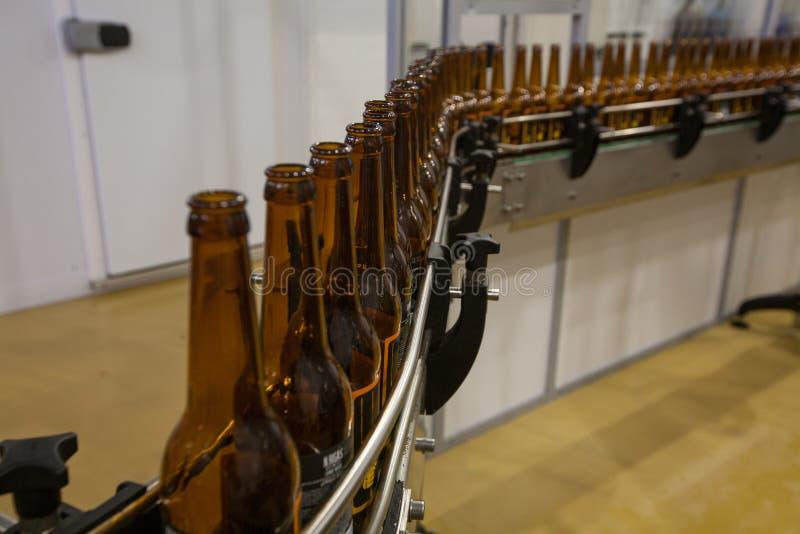 Lege bierflessen, op een transportband, Bindende brouwerij stock foto
