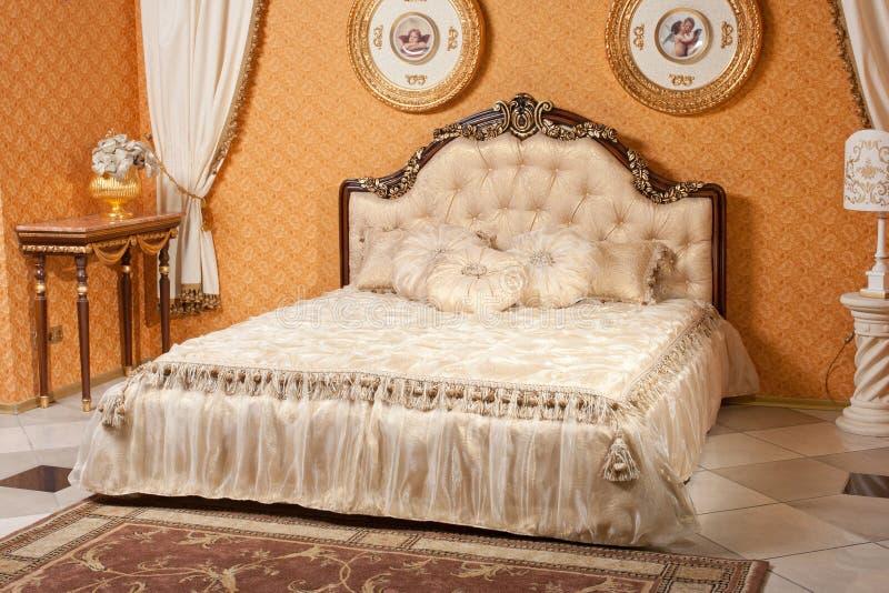 Lege binnenlandse slaapkamerachtergrond in warme die kleuren met klassiek luxemeubilair wordt verfraaid stock afbeelding