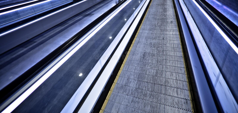 Lege blauwe bewegende roltrap stock foto