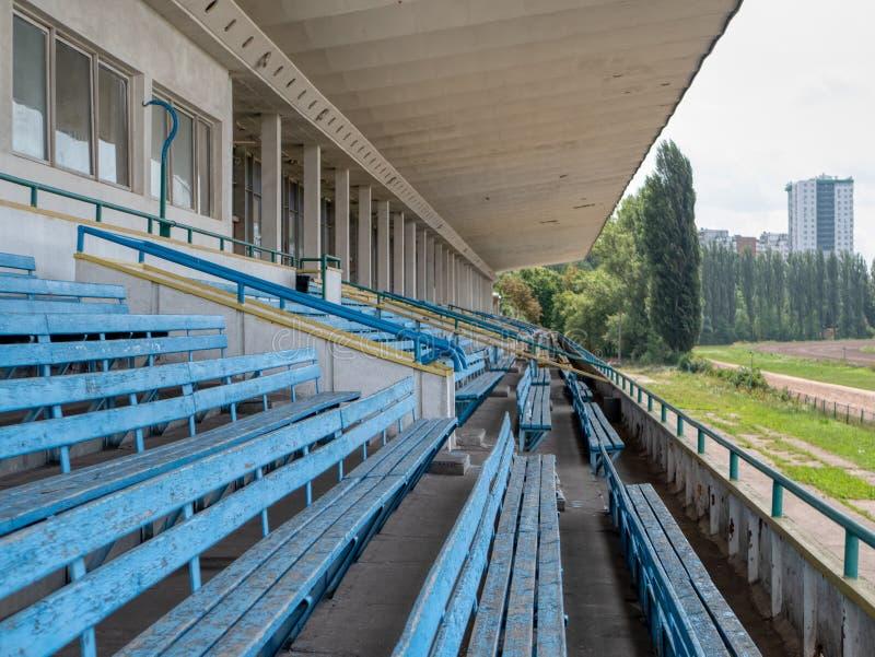 Lege blauwe zetelsbanken bij stadion, renbaan, rasspoor stock afbeelding