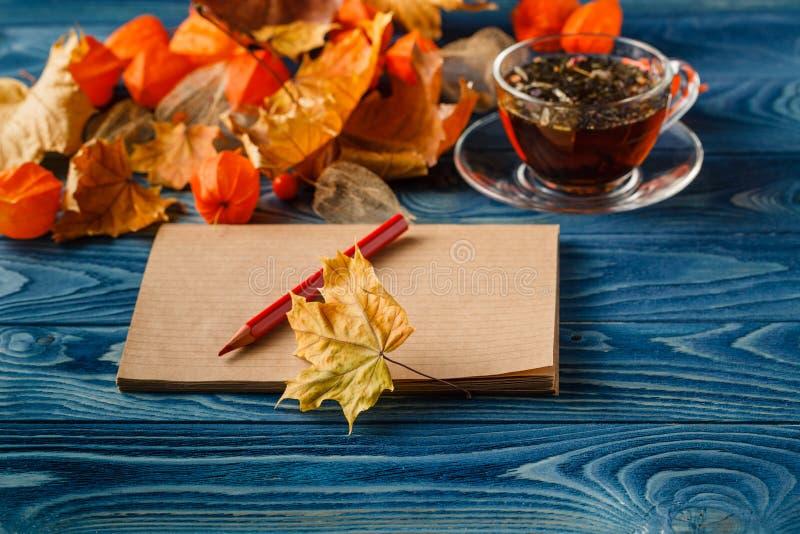 Lege blocnote en de kleurrijke bladeren van de de herfstesdoorn op houten lijst B stock afbeeldingen