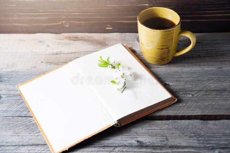 Lege boekdekking op houten achtergrond met de lentebloem en kaap van koffie royalty-vrije stock afbeeldingen