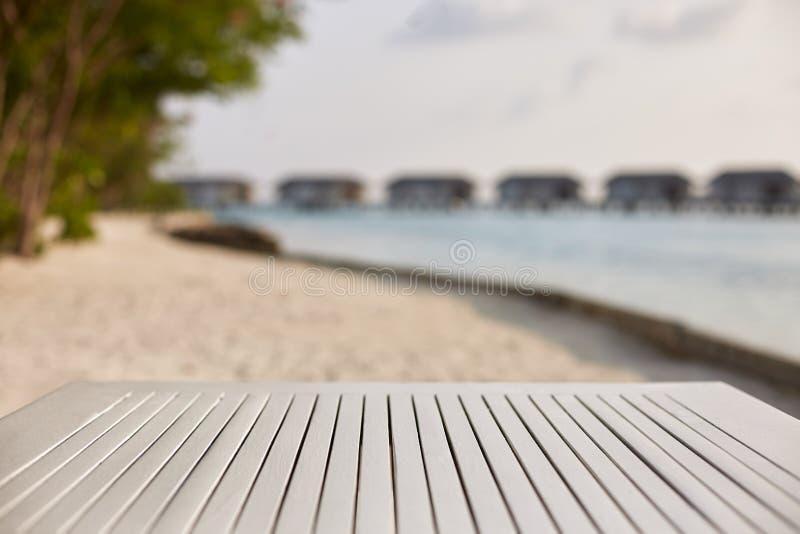 Lege bovenkant van witte houten lijst voor productplaatsing en vertoning Blauwe lagune met waterbungalowwen en tropische installa royalty-vrije stock foto's