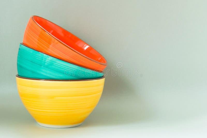 Lege ceramische gekleurde kommen op een grijze achtergrond De ruimte van het exemplaar stock fotografie