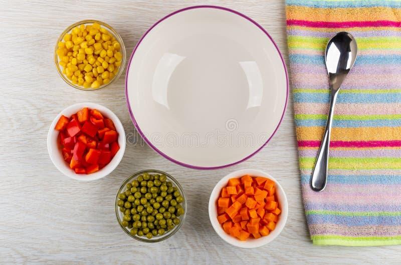 Lege ceramische kom, kommen met stukken van paprika, wortel, groene erwten, graan, lepel op gestreept servet op lijst Hoogste men stock afbeelding