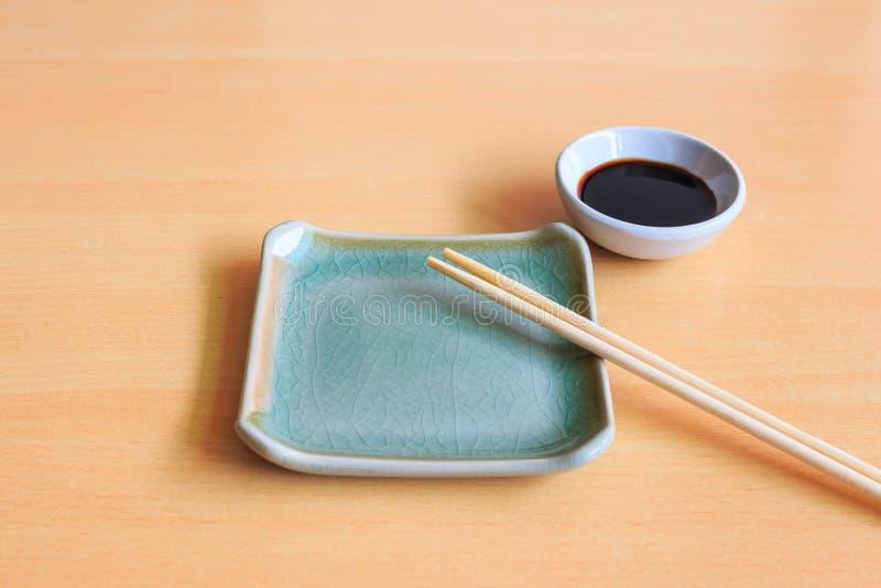 Lege ceramische plaat en bamboeeetstokjes met sojasaus royalty-vrije stock foto's