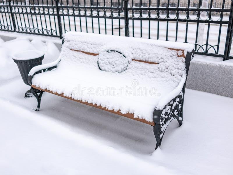 Lege die bank in het de winterpark met verse witte sneeuw wordt behandeld royalty-vrije stock afbeeldingen