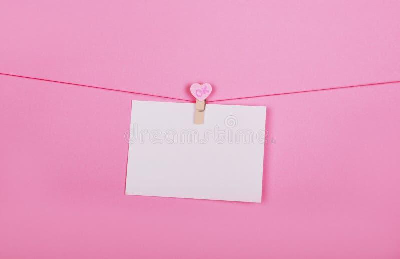 Lege document bladen op een waslijn op een roze achtergrond Roze harten op clothespegs Valentijnskaartendag, het concept van de M royalty-vrije stock fotografie