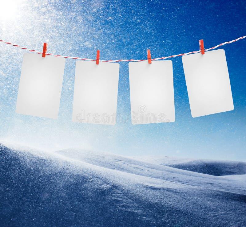 Lege document of fotokaders die op de rode gestreepte kabel hangen Sneeuwstorm op zonnige dagachtergrond stock foto