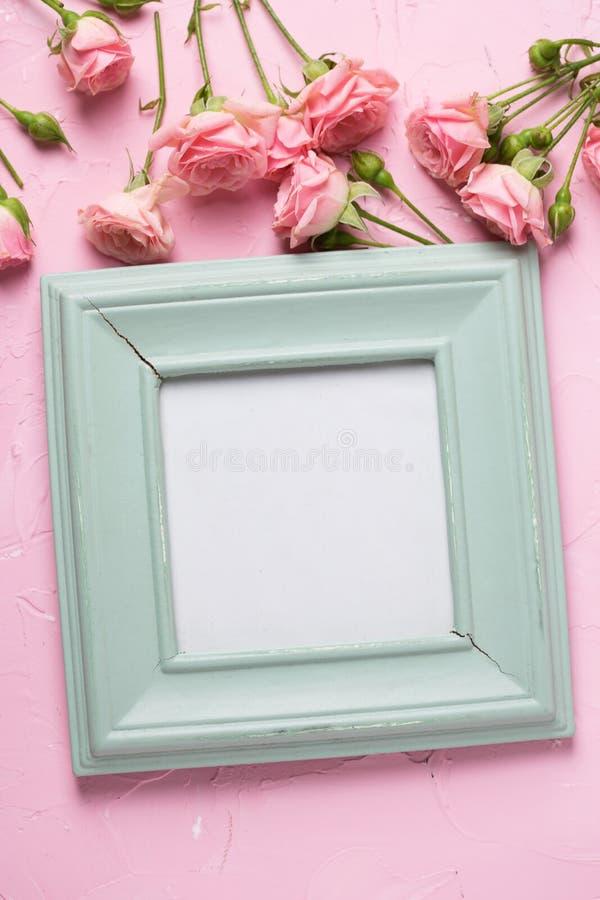 Lege fotokader en grens van roze rozenbloemen op roze t royalty-vrije stock foto