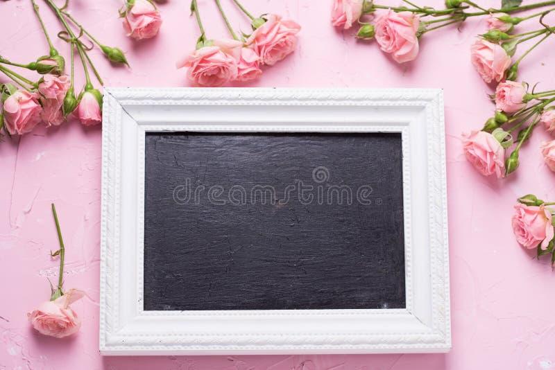 Lege fotokader en grens van roze rozenbloemen op roze t stock foto's