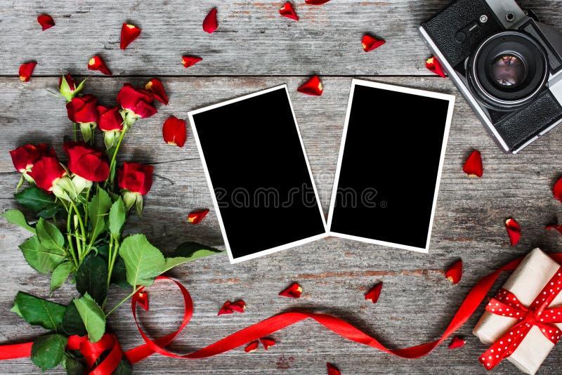 Lege fotokaders, uitstekende retro camera en rode rozenbloemen royalty-vrije stock afbeeldingen