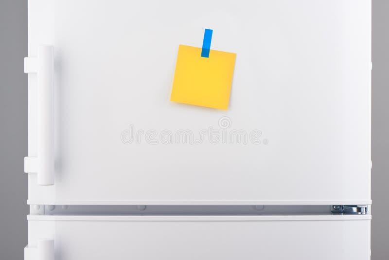 Lege gele document nota en blauwe sticker op witte ijskast royalty-vrije stock afbeeldingen