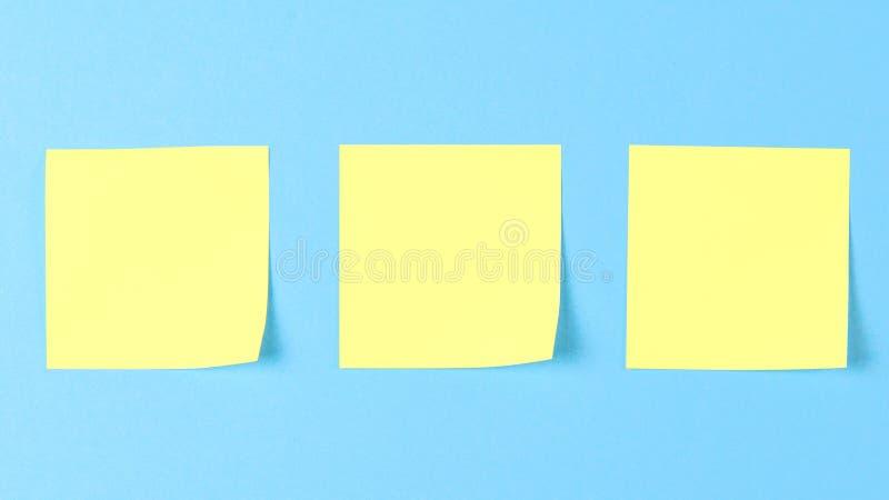 Lege gele kleverige nota's over een blauwe achtergrond, concept het bedrijfswerk Gele memorandumstickers op blauwe muur Model stock foto