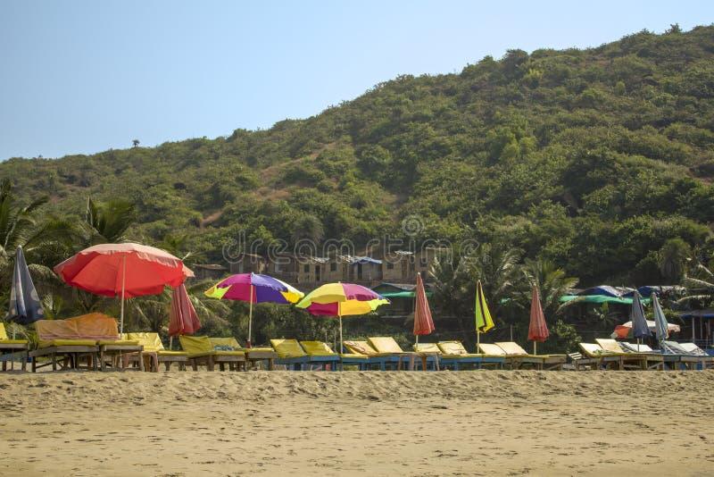 Lege gele zonlanterfanters onder multi-colored strandparaplu's op het gele zand tegen de achtergrond van een groene berg met royalty-vrije stock fotografie