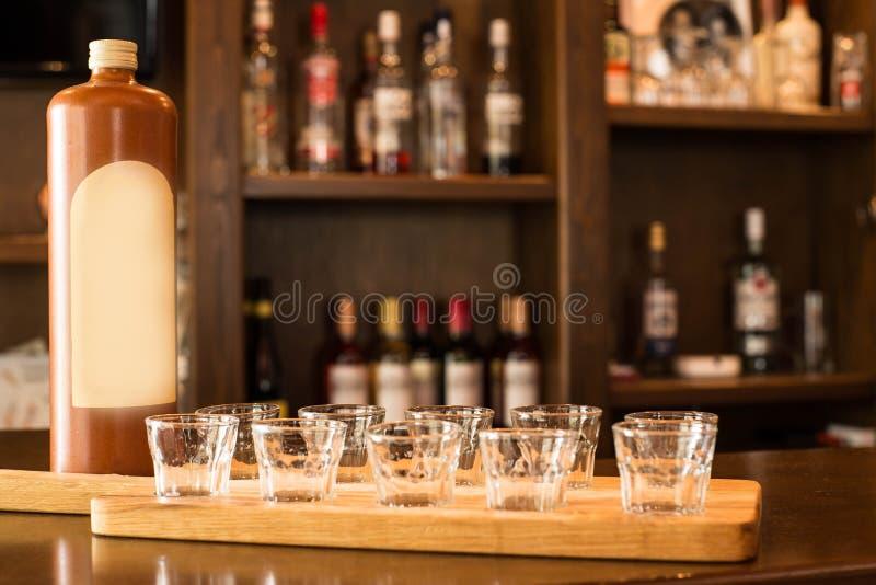 Lege geschotene glazen en alcoholische drank die op de teller op de partij wachten om, in een bar met alcoholische drank op de ac royalty-vrije stock afbeelding