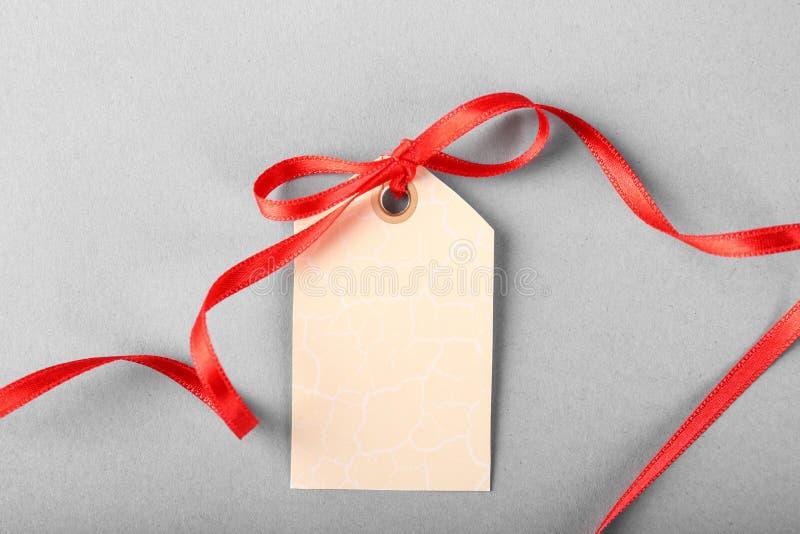 Lege giftmarkering met rood lint op grijze achtergrond royalty-vrije stock foto's