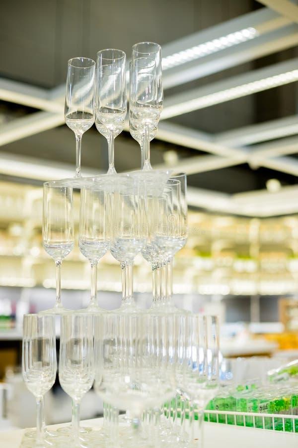 Lege glazen in piramide of toren op lijst bij huwelijksontvangst, alcoholbar, die zich in restaurant richten Piramide van royalty-vrije stock foto's
