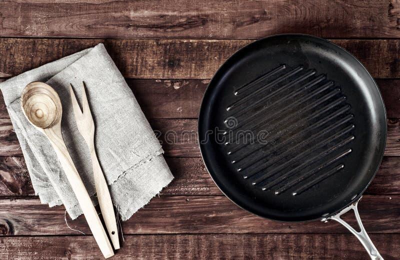 Lege grillpan met houten spatel en lepel stock afbeelding