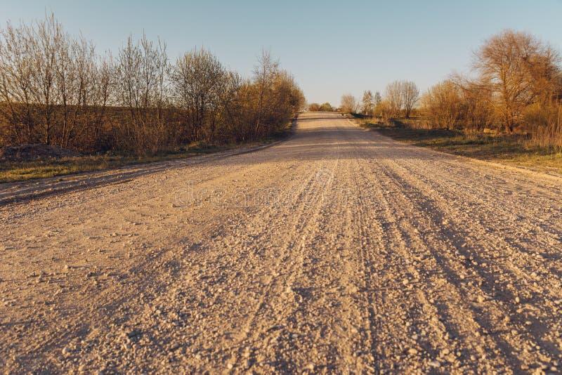Lege grintweg in platteland in perspectief met bomen in su royalty-vrije stock afbeeldingen