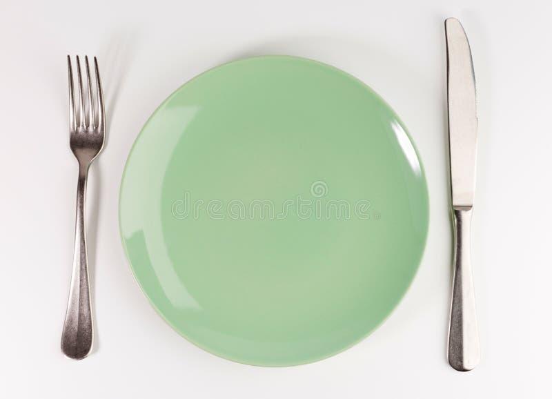 Lege groene plaat met vork en mes dat op witte achtergrond wordt geïsoleerd royalty-vrije stock afbeeldingen