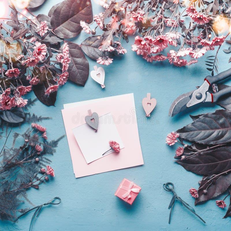 Lege groetkaart op blauw bloemistbureau met roze bloemen, harten en giftdoos Abstract groetconcept Moedersdag, Verjaardag royalty-vrije stock foto