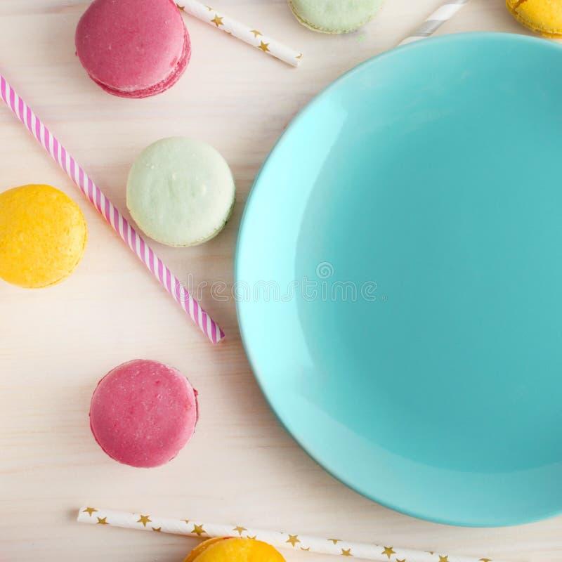 Lege heldere blauwe plaat, met een heerlijk rond dessert, makarons en buizen voor een cocktail Plaats voor tekst feestelijk stock afbeelding