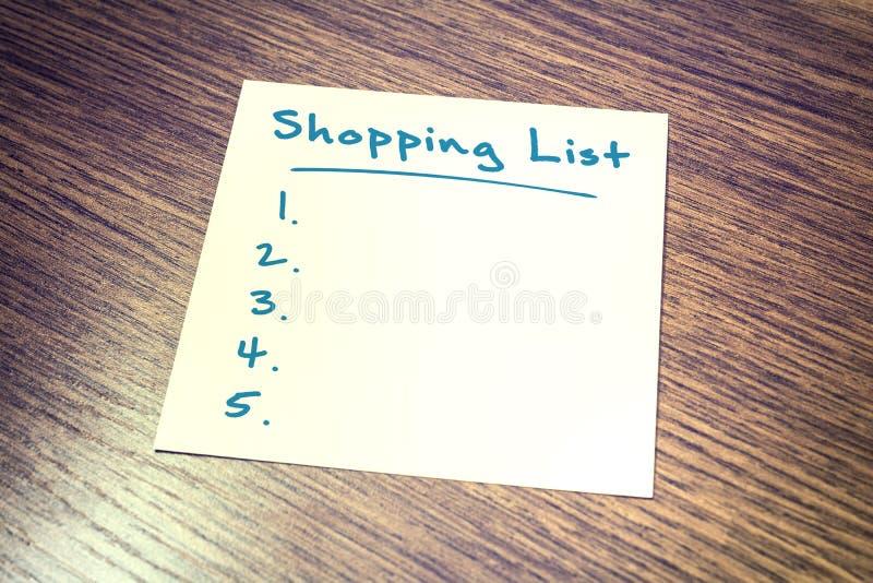 Lege het Winkelen Lijstherinnering die op papier op Houten Kast liggen stock afbeelding